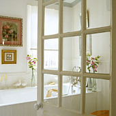 View through Georgian glazed door into a white bathroom - Stock Image - B8HHFG
