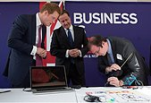 "epa03700460 Britain's Prince Harry (L) and British Prime Minister David Cameron watch Max Bogue (R), co-found and CEO of 3Doodler, demonstrate a 3D printing device during a meeting with entrepreneurs at the ""GREAT Event"" in Manhattan, New York, USA, on 14 May 2013.  EPA/BRENDAN MCDERMID / POOL - Stock Image - D82KFD"