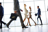 White collar workers going down office corridor during working day - Stock Image - DYN8WY