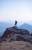 Walker silhouetted on the summit of Slieve Bearnagh, Mourne Mountains, Co Down, Northern Ireland - Stock Image - A5XDAD