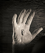 dirty hand holding small key - Stock Image - B0RXRC