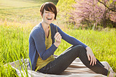A young woman sitting in an open space, a grass field, on a blanket. - Stock Image - DGMRBC