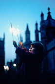 Young girl holding a sparkler on Guy Fawkes Night - Stock Image - ANPR7C