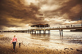 Contrasted lifestyle imagery of a woman walking dog on stormy beach by large jetty. Taken Redcliffe, Queensland Australia - Stock Image - EXKNKM