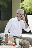 Businessman talking on phone at lunch - Stock Image - E8FRXK