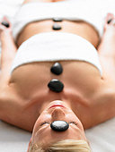 A woman lying in a spa with stones on her body - Stock Image - AH12KP