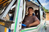 Bus driver smiling at window - Stock Image - CN7NGP