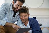 Smiling homosexual couple using digital tablet - Stock Image - ERBP7W