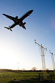 Low angle view of commercial aircraft flying over approach lights. - Stock Image - BEGR1T