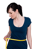 young woman measuring her waist with a tape measure - Stock Image - A32T4Y