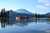 Couple paddling canoe on lake - Stock Image - AB0GYP
