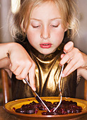 A girl eating food. - Stock Image - BAB8G5