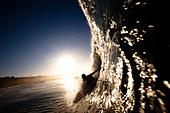 A male surfer pulls into a barrel at Zuma beach in Malibu, California. - Stock Image - BXD6NT