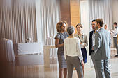 Business people standing in conference room, talking and smiling - Stock Image - ECX768