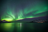 Aurora Borealis The Northern Lights fill the sky at Kvaloya in the Arctic Circle near Tromso, Northern Norway - Stock Image - CRXCG5