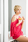 young woman eating grapefruit - Stock Image - BC729R