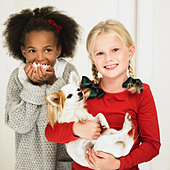 Girls eating popcorn and holding dog - Stock Image - D2AH4D