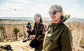 Young male and female hikers with camera enjoying views - Stock Image - E5WR7A
