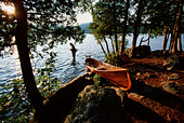 Fisherman wading in lake with canoe on shore - Stock Image - BPDFCD
