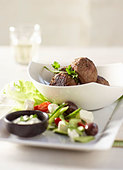 Meatballs with herb dip and Greek salad - Stock Image - BJJA84