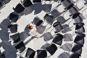Woman standing in spiral of office chairs - Stock Image - B3KW5K
