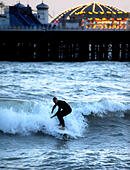 Brighton, Sussex, UK. 28 October, 2014. - UK weather. A surfer makes the most of the conditions under the lights of Brighton Pier early this evening after a warm sunny day on the coast  © Simon Dack/Alamy Live News - Stock Image - E9J12M