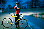 Young female cyclist drinking from water bottle at velodrome track - Stock Image - E0A7WF