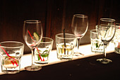 Still Life of Many Beverage Glasses on a Bottom Lit Shelf after a Party - Stock Image - AJXMMG