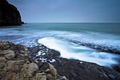 Waves surge into a large rock pool on Dancing Ledge, Purbeck, Dorset - Stock Image - AEPJEY