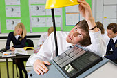 Student experimenting with solar panel and light in science class - Stock Image - C92GWN