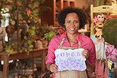 African American business owner standing in shop holding open sign - Stock Image - CEDCXT