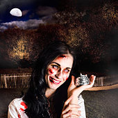 Creepy deceased zombie woman holding silver service bell in a spooky graveyard location in a depiction of death services - Stock Image - DTKM1K