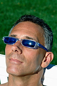Head and Shoulders Portrait of a Man Soaking in the Sun He is Wearing Sunglasses - Stock Image - B4BEE9