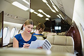 Young businesswoman reading documents in airplane - Stock Image - D8KT95