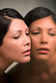 Young Hispanic woman and her mirror reflection - Stock Image - BK7MNH