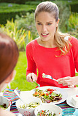 Woman Having Lunch in Garden with Friend - Stock Image - DTA0XK