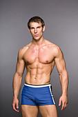 Portrait of shirtless fitness instructor wearing blue shorts, studio shot - Stock Image - CW55DG