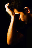 Depressed young man head in hand - Stock Image - B730EY