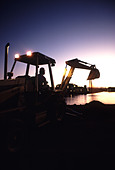 A silhouette of a man operating a backhoe at sunrise - Stock Image - AE9YCR