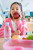 girl eating lunch at school - Stock Image - BD2CK6