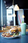 Cheeseburger, french fries and milkshake in diner - Stock Image - C8NNHJ