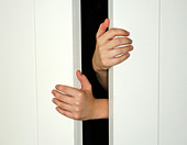 Two hands holding open or close white doors - Stock Image - B0AE47