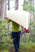 A man portages his canoe through Wabakimi Provincial Park, Ontario, Canada - Stock Image - CFCRY0