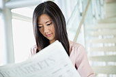 Businesswoman reading newspaper in office - Stock Image - DCFPYP