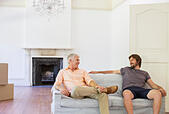 Father and son sitting on couch in living space - Stock Image - E775J0