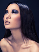 Beauty portrait of an asian woman with sparkling black eyeshadows and black hair - Stock Image - CP0E9J