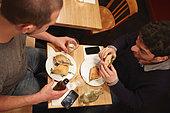 Two men having lunch in restaurant, elevated view - Stock Image - EKHX42
