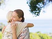 Women hugging outdoors - Stock Image - E59RF0