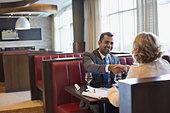 Business people shaking hands at hotel restaurant table - Stock Image - DFD9MP