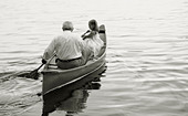 Grandfather and granddaughter paddling in canoe on lake. - Stock Image - A697HX